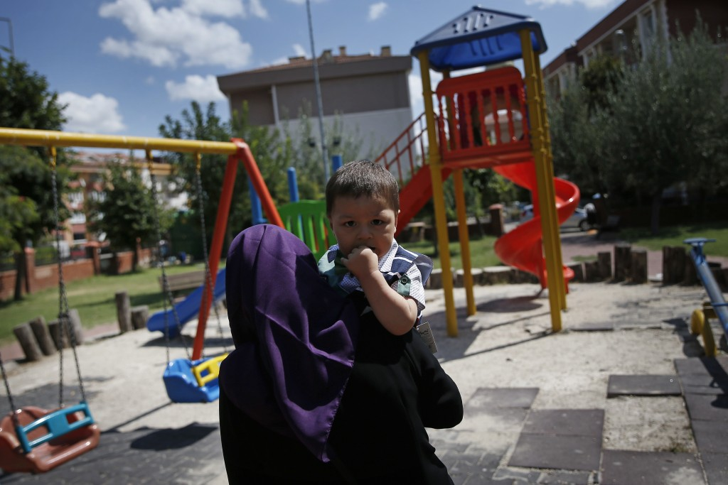 In this Aug. 21, 2018, photo, Meripet, 29, carries her son Abduweli, at a playground in Istanbul, Turkey. Meripet came to Turkey in February 2017 to v...