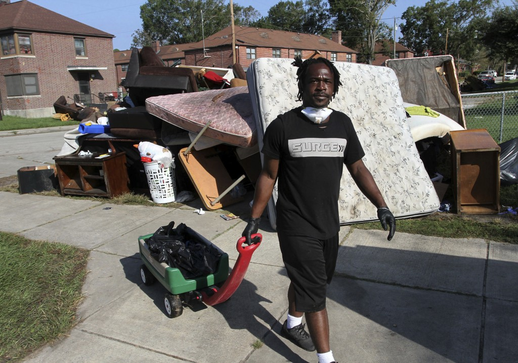 Volunteer Johnnie Evans brings a wagon of water to cleanup crews helping with the grisly task of removing storm damaged belongings, spoiled food and s