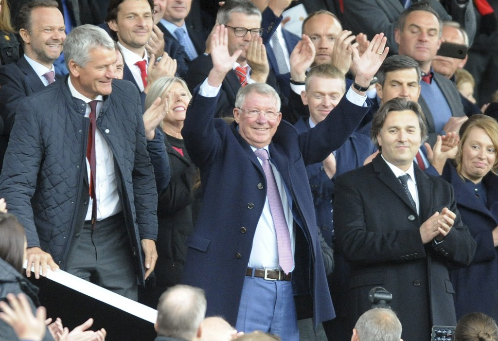 Former Manchester United manager Alex Ferguson waves as he takes his seat on the stands before the English Premier League soccer match between Manches...