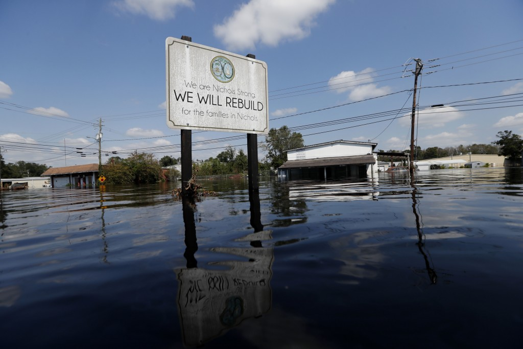 A sign commemorating the rebuilding of the town of Nichols, which was flooded two years earlier from Hurricane Matthew, stands in floodwaters in the a
