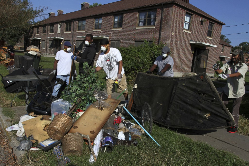 Cleanup crews work to remove storm damaged belongings, spoiled food and soaked furniture at Trent Court Apartments in New Bern, N.C., Sept. 21, 2018.