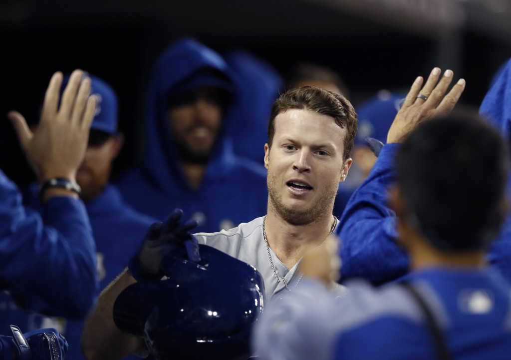Kansas City Royals' Brett Phillips is greeted in the dugout after scoring during the eighth inning of the team's baseball game against the Detroit Tig