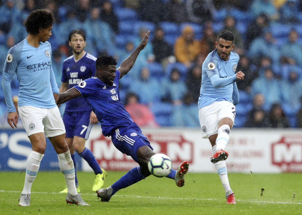 Manchester City's Riyad Mahrez, right, scores against Cardiff City during the English Premier League soccer match at The Cardiff City Stadium, Saturda...