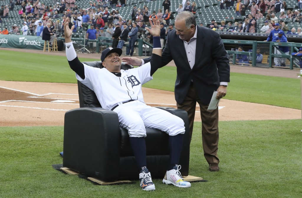 Detroit Tigers designated hitter Victor Martinez is presented a chair by Al Avila, executive vice president of baseball operations and general manager