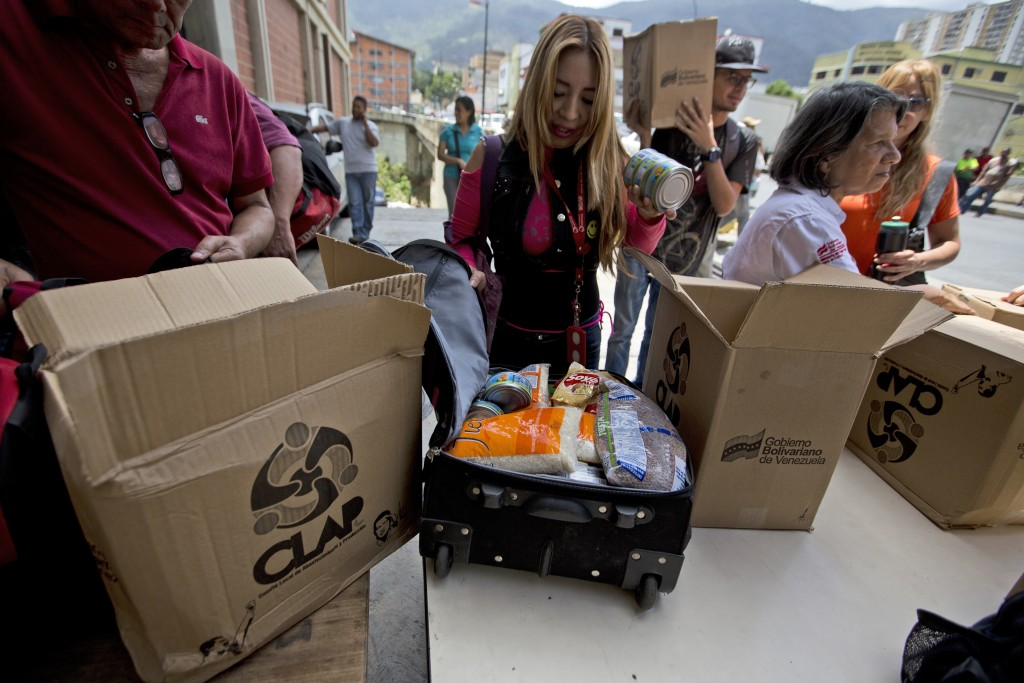 In this July 6, 2018 photo, employees of a government-supported cultural center receive boxes with subsided food distributed under a government progra...