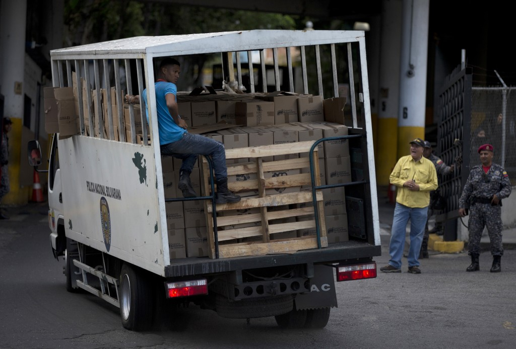 In this May 16, 2018 photo, a Bolivarian National Police truck drives into headquarters loaded with boxes with subsided food distributed under the gov...