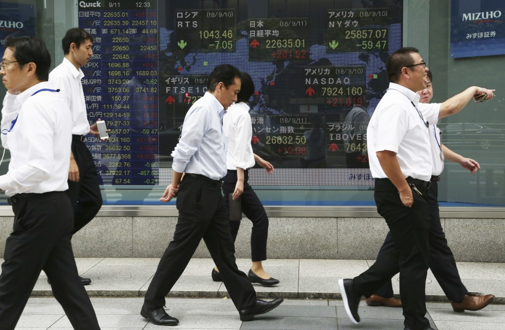 In this Sept. 11, 2018, photo, people walk by an electronic stock board of a securities firm in Tokyo. Shares have fallen in Asia after China rebuffed