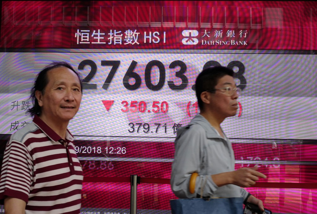 People walk past an electronic board showing Hong Kong share index outside a local bank in Hong Kong, Monday, Sept. 24, 2018. Shares have fallen in As