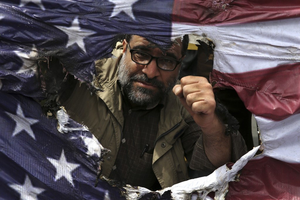 FILE - In this May 11, 2018 file photo, an Iranian protestor clenches his fist behind a burnt representation of the U.S. flag during a protest over U....