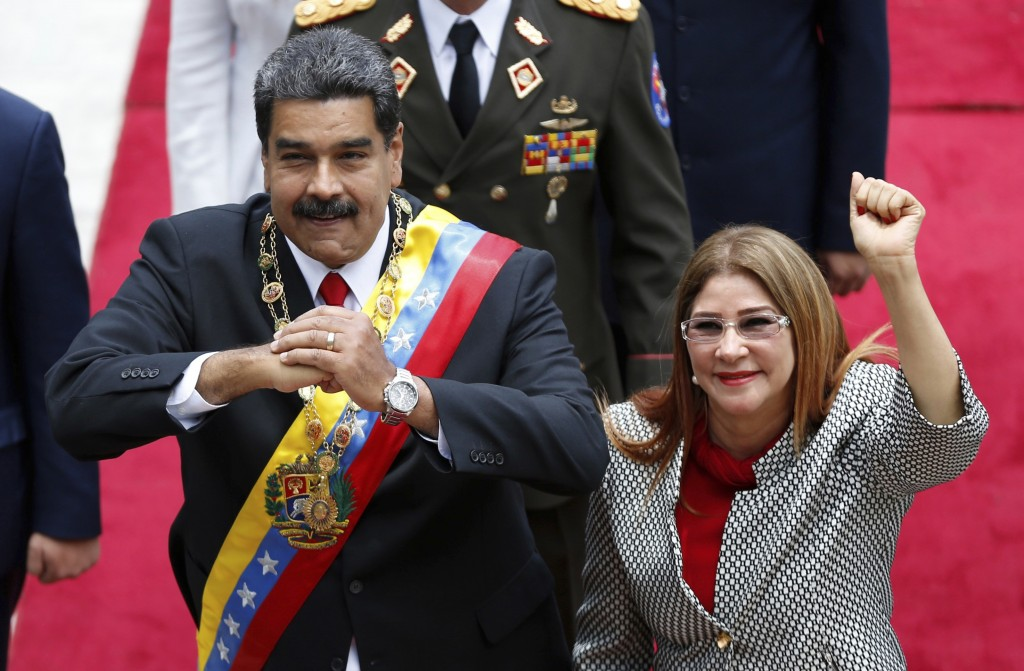 FILE - In this May 24, 2018 file photo, Venezuela's President Nicolas Maduro, left, and first lady Cilia Flores, acknowledge the press corps as they a...