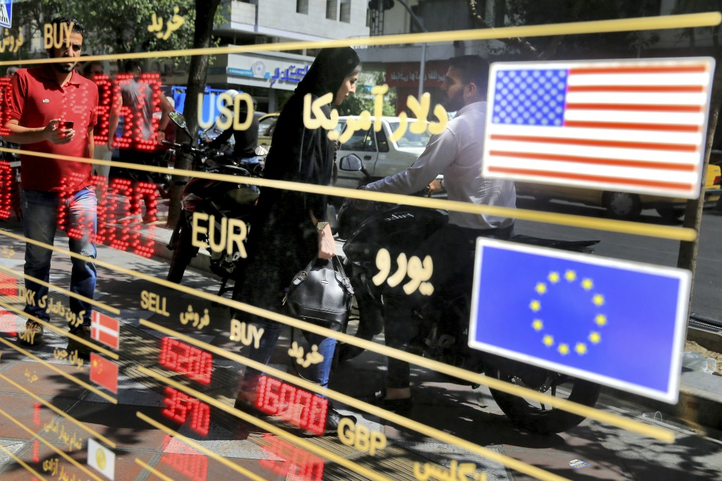 FILE - In this Wednesday, Sept. 5, 2018 file photo, various currency rates are displayed at a window of an exchange shop in downtown Tehran, Iran. Ira...