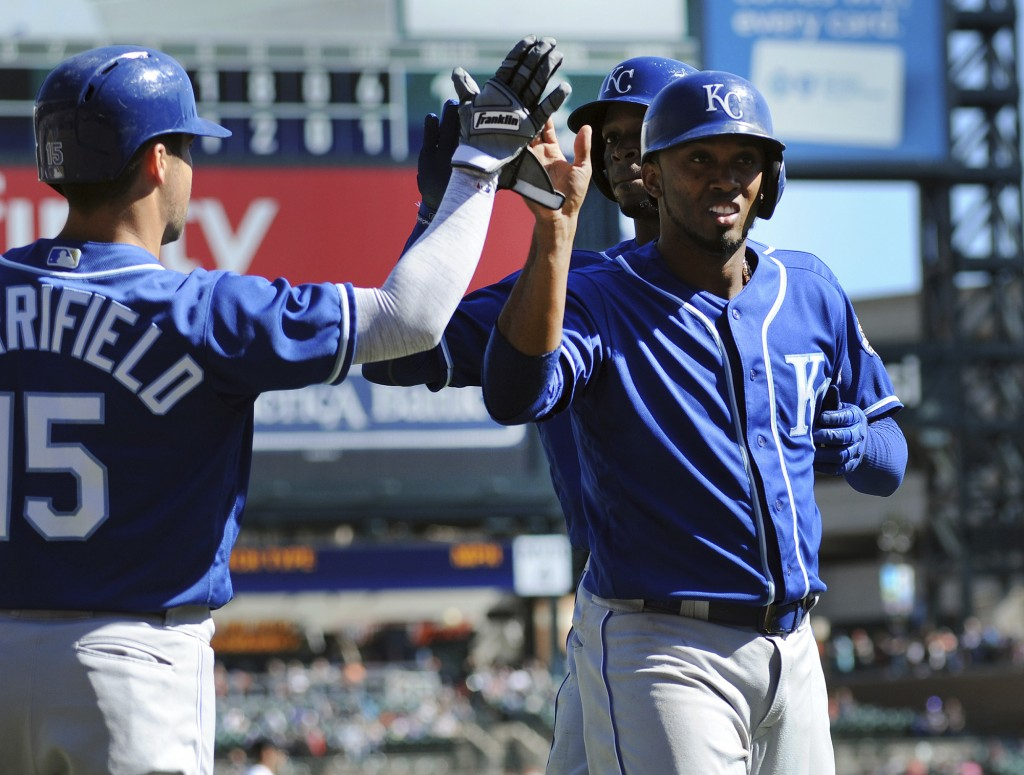 Kansas City Royals' Alcides Escobar, right, and Rosell Herrera are congratulated by Whit Merrifield (15) after they scored on a single by Cam Gallaghe