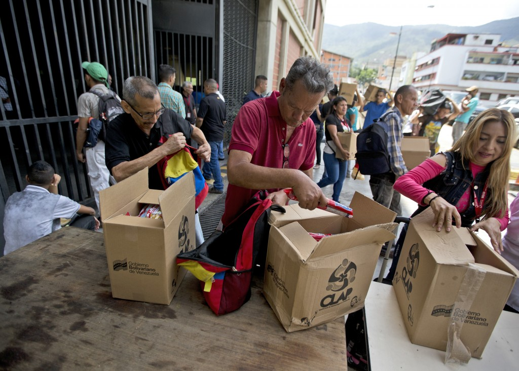 In this July 6, 2018 photo, employees of a government-supported cultural center collect their boxes with subsided food distributed under government pr...