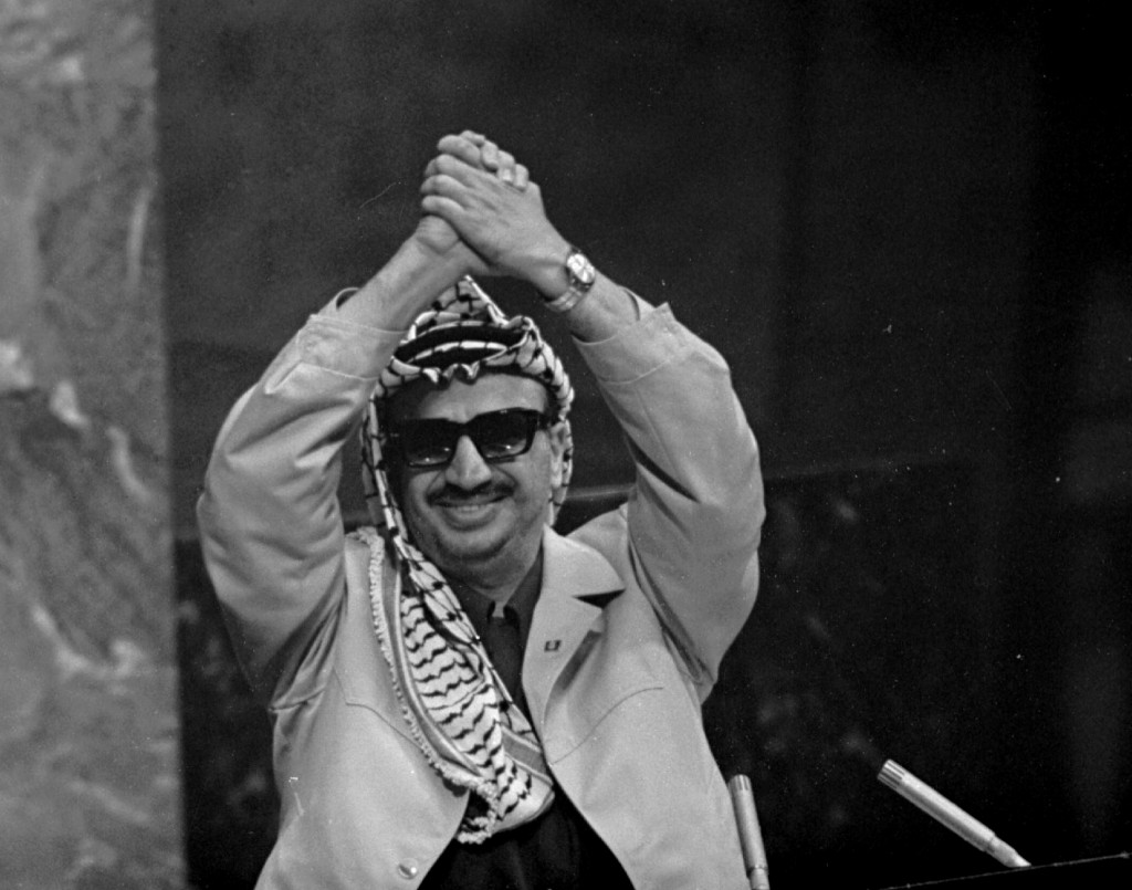 FILE - In this Nov. 13, 1974 file photo, Yasser Arafat clasps his arms over his head as he addresses the United Nations General Assembly, at U.N. head