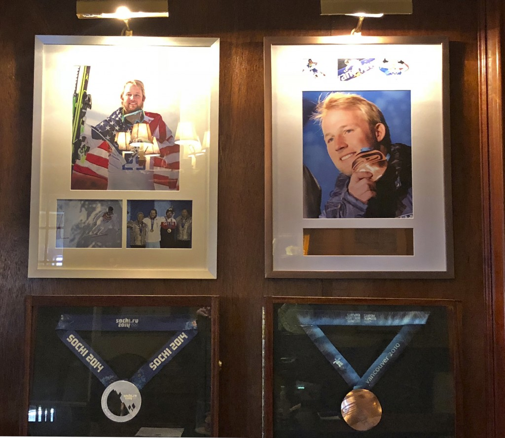 In this Sept. 1, 2018, photo, Olympic silver and bronze medals won by former U.S. skier Andrew Weibrecht hang behind the front desk of the Mirror Lake...