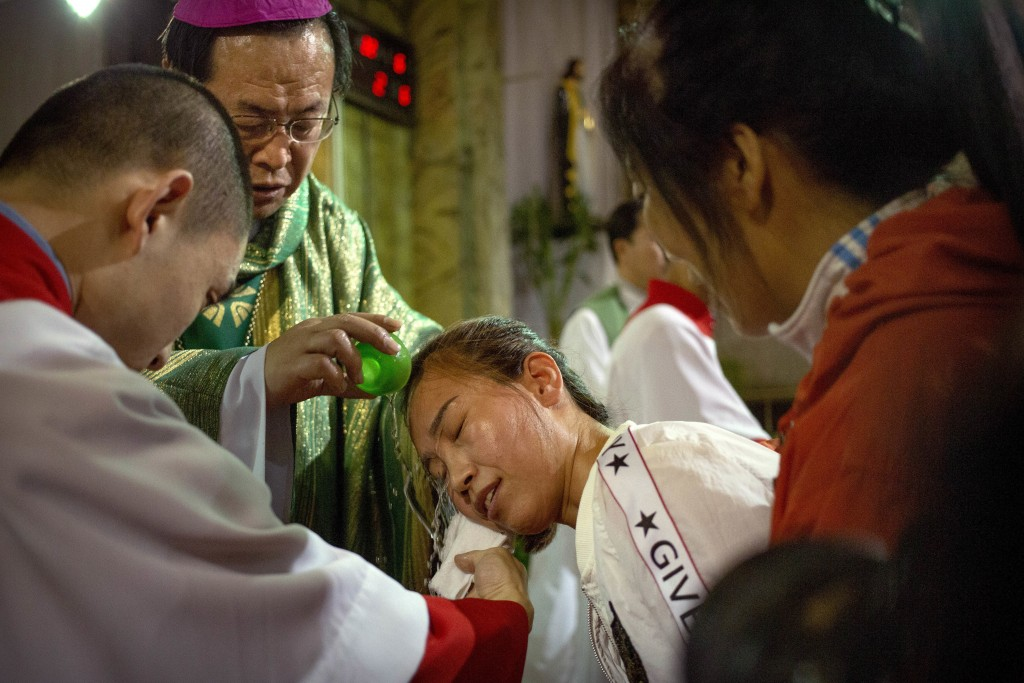 In this Sept. 22, 2018, file photo, Chinese bishop Joseph Li Shan, top left, baptizes a member of the faithful during a mass at the Cathedral of the I...