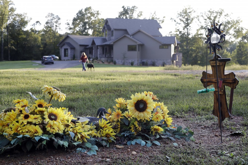 In this Sept. 25, 2018, photo, the grave of Sonny Melton is decorated with sunflowers on the grounds of the home Sonny and his wife, Heather, built in...