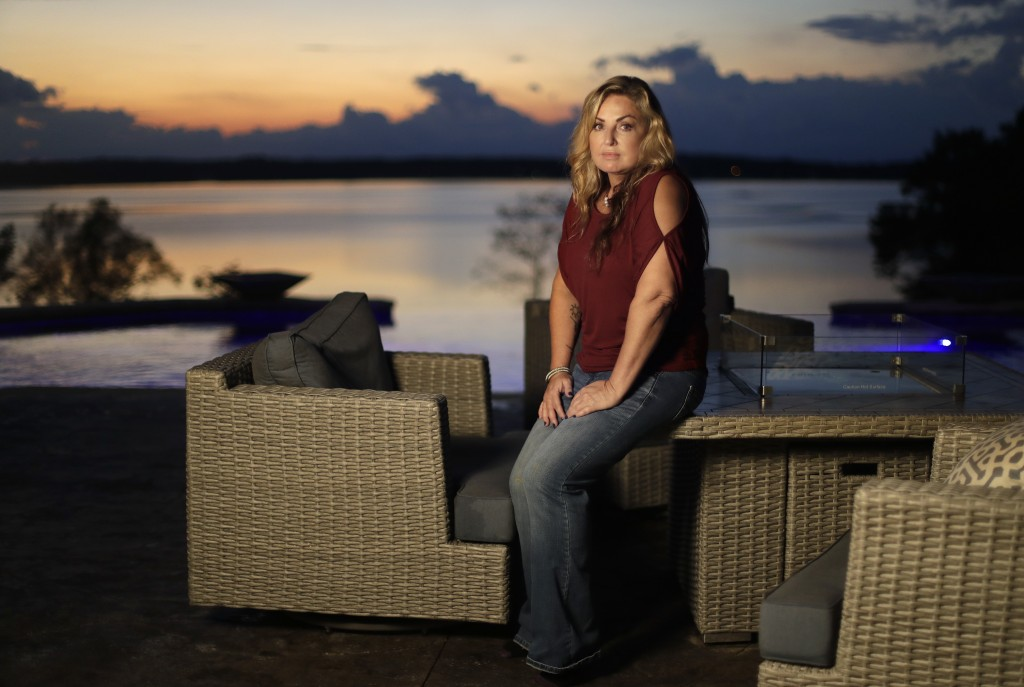 In this Sept. 25, 2018, photo, Heather Melton sits on a patio at her home in Big Sandy, Tenn., as the sun sets over the Big Sandy River. Heather and h...
