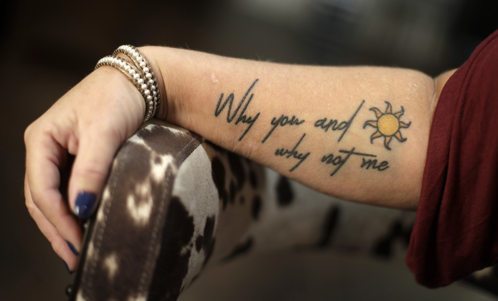 In this Sept. 25, 2018, photo, Heather Melton shows a tattoo bearing a lyric by country singer Eric Church at her home in Big Sandy, Tenn. Eric Church...