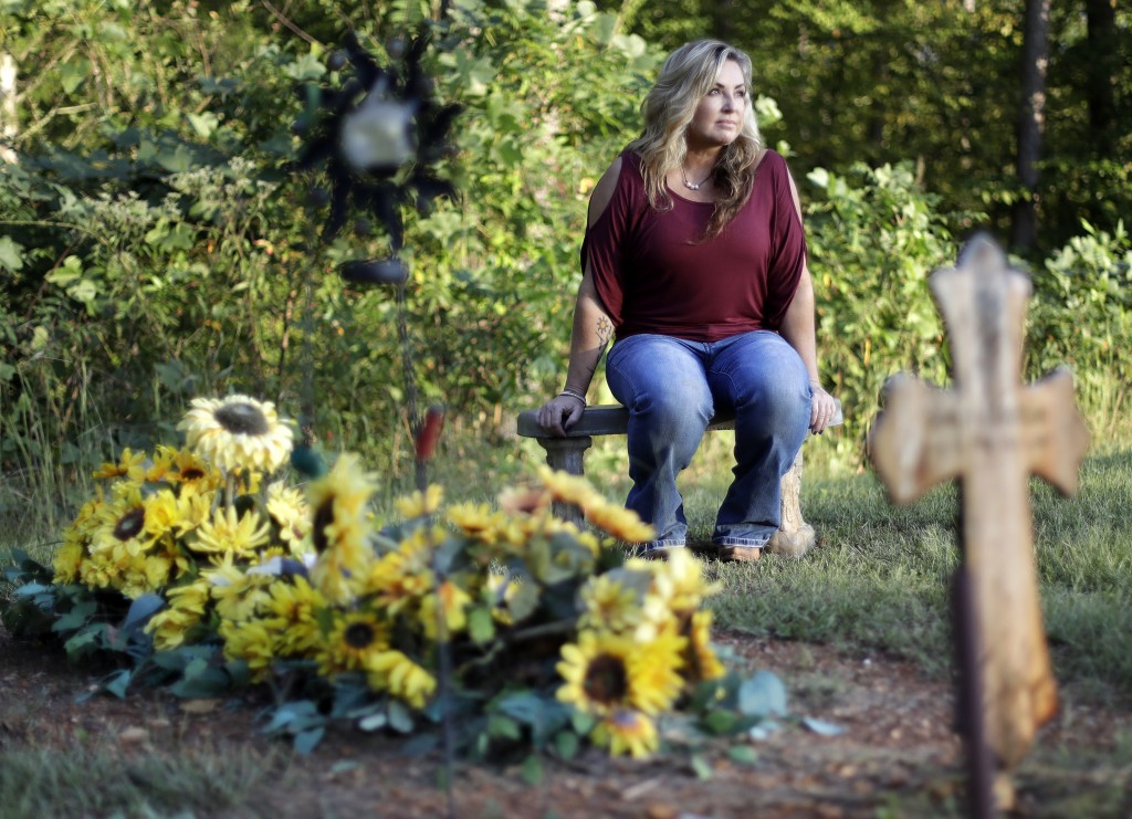 In this Sept. 25, 2018, photo, Heather Melton sits by the grave of her husband, Sonny, on the grounds of her home in Big Sandy, Tenn. Sonny Melton die...