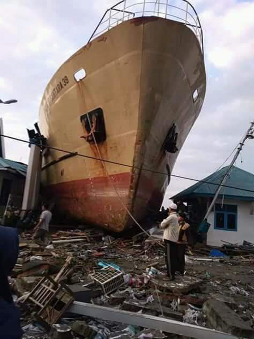 In this Saturday, Sept. 29, 2018, file photo, villagers view a ship swept ashore by a tsunami in Palu, Central Sulawesi, Indonesia. (AP Photo/Rio Mari...