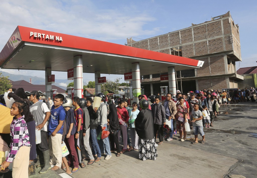 In this Sunday, Sept. 30, 2018, file photo, people queue for gasoline following a massive earthquake and tsunami in Palu, Central Sulawesi, Indonesia....
