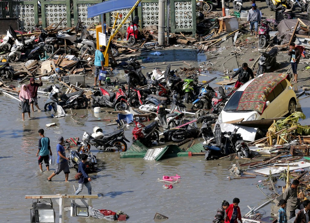 People survey damage outside the shopping mall following earthquakes and tsunami in Palu, Central Sulawesi, Indonesia, Sunday, Sept. 30, 2018. Rescuer