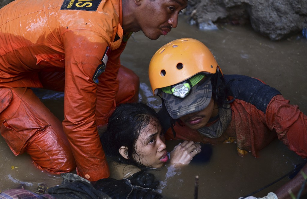 In this Sunday, Sept. 30, 2018, file photo, rescuers try to rescue a 15-year old earthquake victim Nurul Istikharah from flood water in her damaged ho