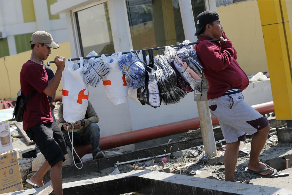 In this Sunday, Sept. 30, 2018, file photo, workers carry goods from their shop at a shopping mall damaged by a massive earthquake and a tsunami in Pa...