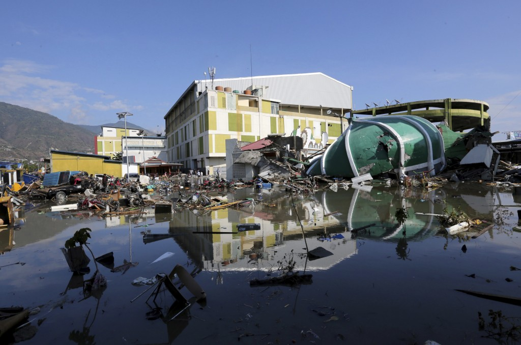 In this Sunday, Sept. 30, 2018, file photo, a damaged shopping mall sits in flood water following earthquakes and a tsunami in Palu, Central Sulawesi,...