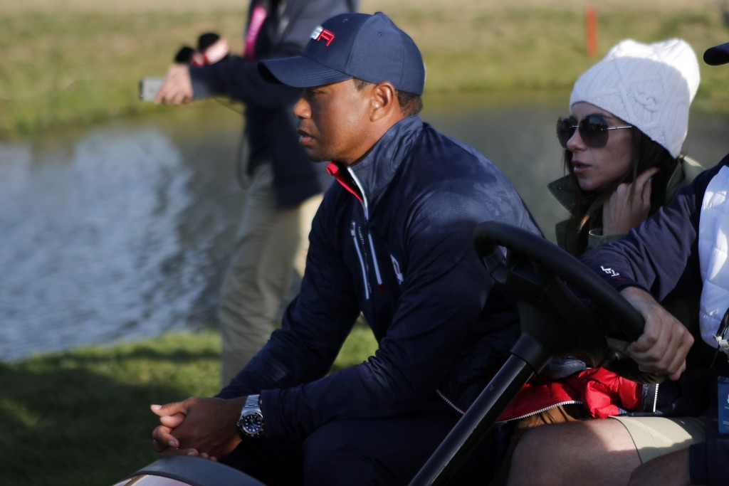 Tiger Woods of the US and his partner Erica Herman ride a golf cart during a foursome match on the second day of the 2018 Ryder Cup at Le Golf Nationa...