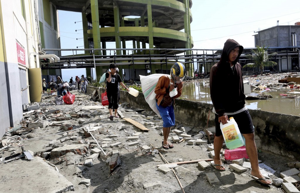 In this Sunday, Sept. 30, 2018, file photo, people carry away items from a shopping mall badly damaged by a massive earthquake and tsunami in Palu, Ce...