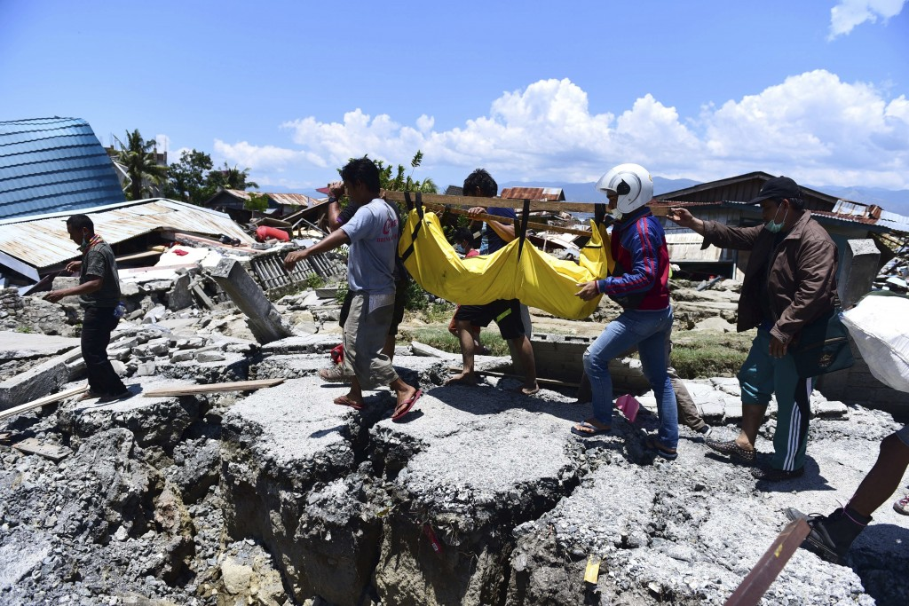 In this Sunday, Sept. 30, 20128, file photo, villagers carry the body of a victim following earthquakes and tsunami in Palu, Central Sulawesi, Indones