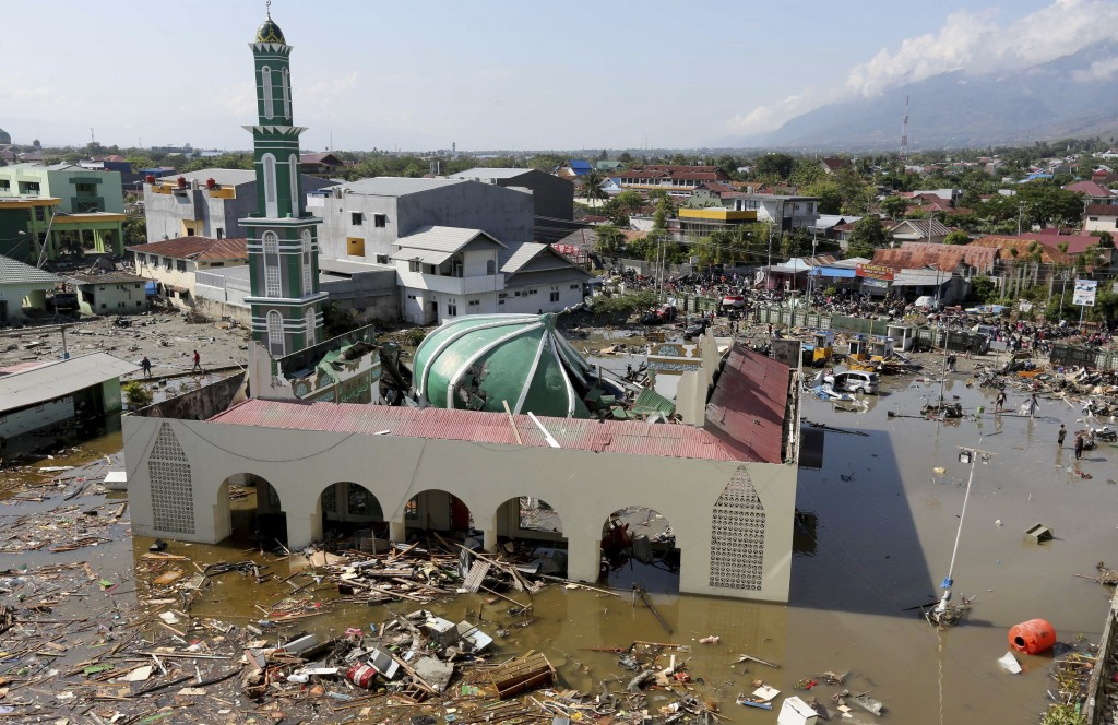 In this Sunday, Sept. 30, 2018, file photo, people survey the mosque damaged in a massive earthquake and a tsunami in Palu, Central Sulawesi, Indonesi