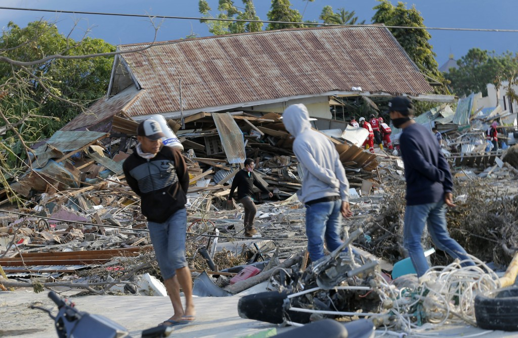 People survey the damage to a residential area following a massive earthquake and tsunami at Talise beach in Palu, Central Sulawesi, Indonesia, Monday...