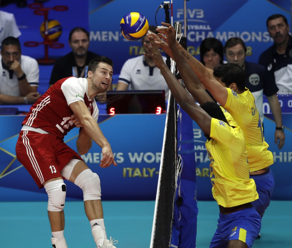 Poland's Michal Kubiak, left, hits the ball during the Men's World Championships volleyball final match between Brazil and Poland, in Turin, Italy, Su...