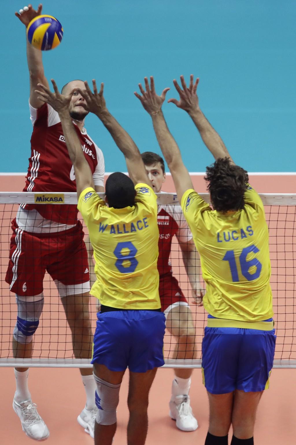 Poland's Bartosz Kurek hits the ball as Brazil's Wallace De Souza, left, and Brazil's Lucas Saatkamp, right, jump to block the ball during the Men's W...