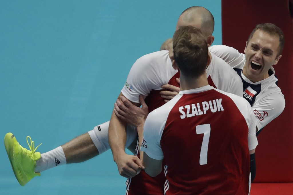 Poland's Fabian Drzyzga, right, jumps on the back of Bartosz Kurek, after their team won the first set in the Men's World Championships volleyball fin...