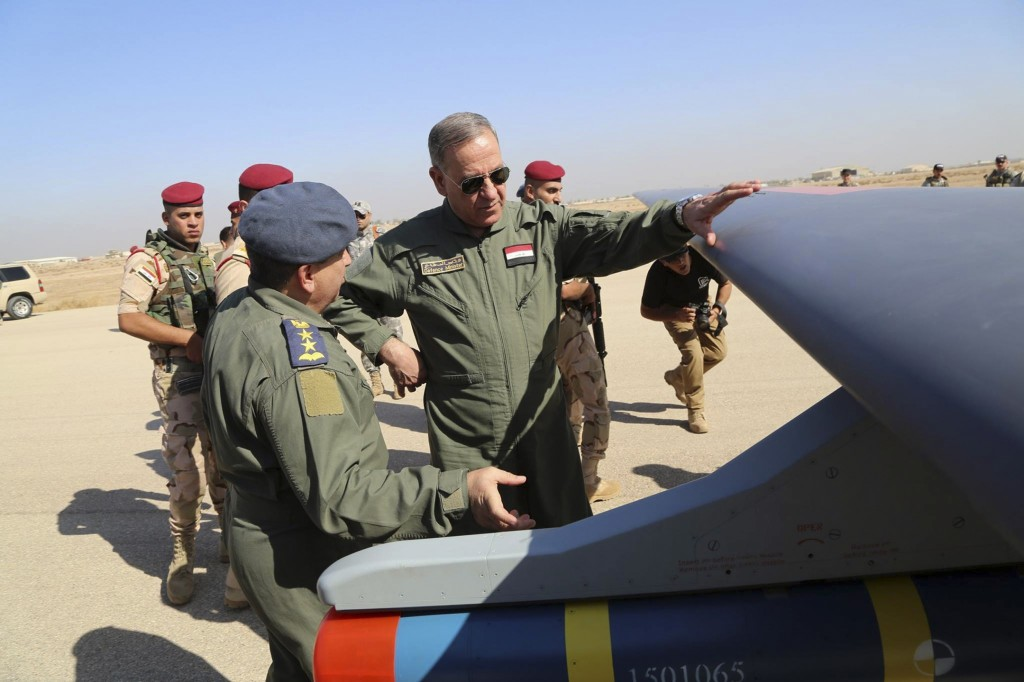 FILE - In this Oct. 10, 2015, file photo, Iraqi Defense Minister Khaled al-Obeidi, center, inspects a first Chinese drone to be used by the Iraqi Air ...