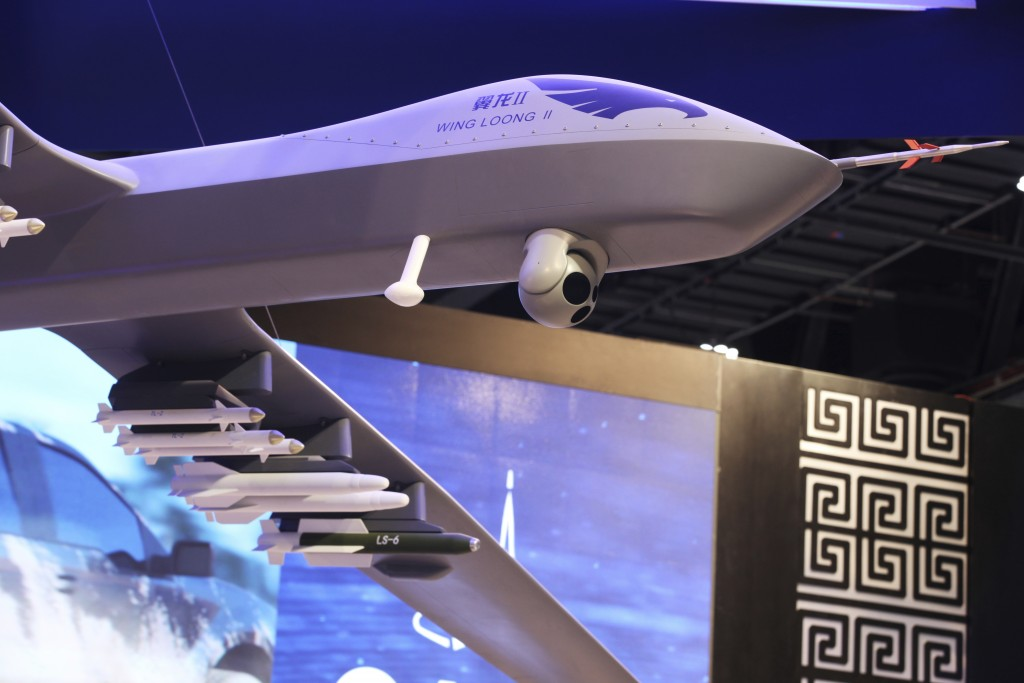 FILE - In this Sunday, Feb. 25, 2018, file photo, a model of the Wing Loong II weaponized drone hangs above the stand for the China National Aero-Tech...