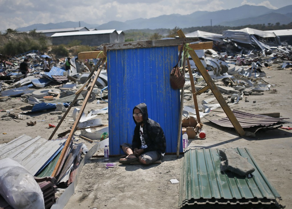 In this Wednesday, Oct. 3, 2018, photo, a man sits in the shade of a sheet of a corrugated tin surrounded by earthquake debris in Palu, Central Sulawe