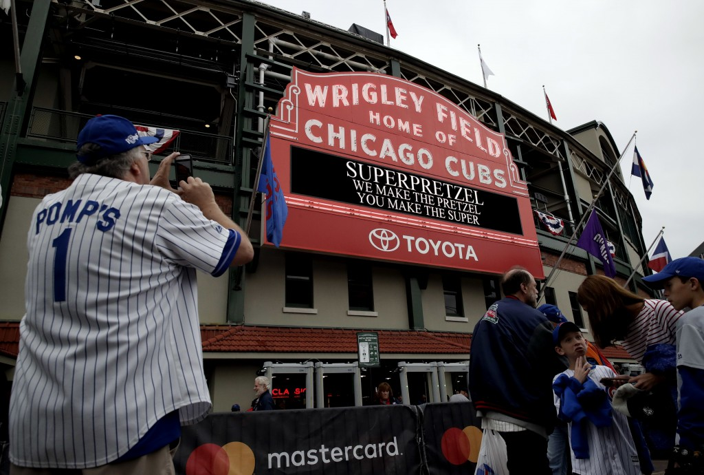Chicago Cubs fans wait outside Wrigley Field before the National League wild-card playoff baseball game between the Colorado Rockies and the Chicago C...