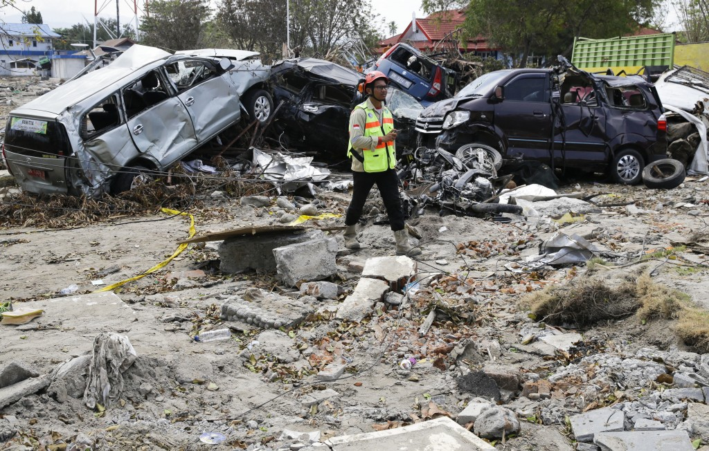 A man walks past remains of cars that were destroyed in the massive earthquake and tsunami that hit Palu, Central Sulawesi, Indonesia Thursday, Oct. 4...