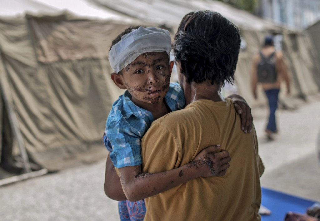 In this Thursday, Oct. 4, 2018, file photo, a boy injured during the tsunami is carried by his relative at a makeshift hospital in Palu, Central Sulaw...