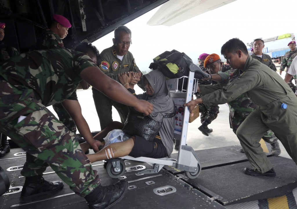 A woman is assisted on to an Indonesia Air Force cargo plane at the Mutiara Sis Al-Jufri airport to evacuate the earthquake and tsunami-damaged city o...