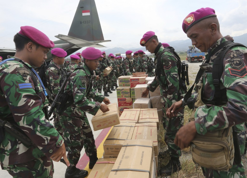 Indonesian military personnel help distribute relief aid at the Mutiara Sis Al-Jufri airport to evacuate the earthquake and tsunami-damaged city of Pa...