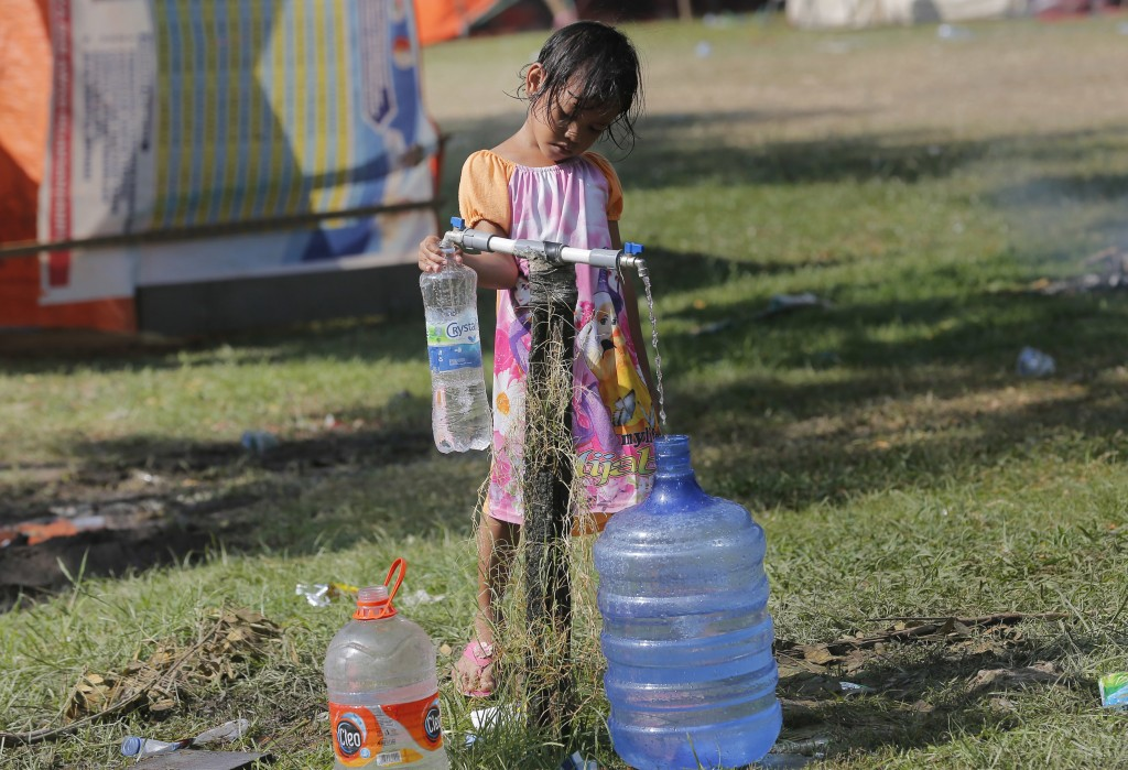 A girl fills water jugs at a temporary shelter in Palu, Central Sulawesi Indonesia, Thursday, Oct. 4, 2018. Life is on hold for thousands living in te...
