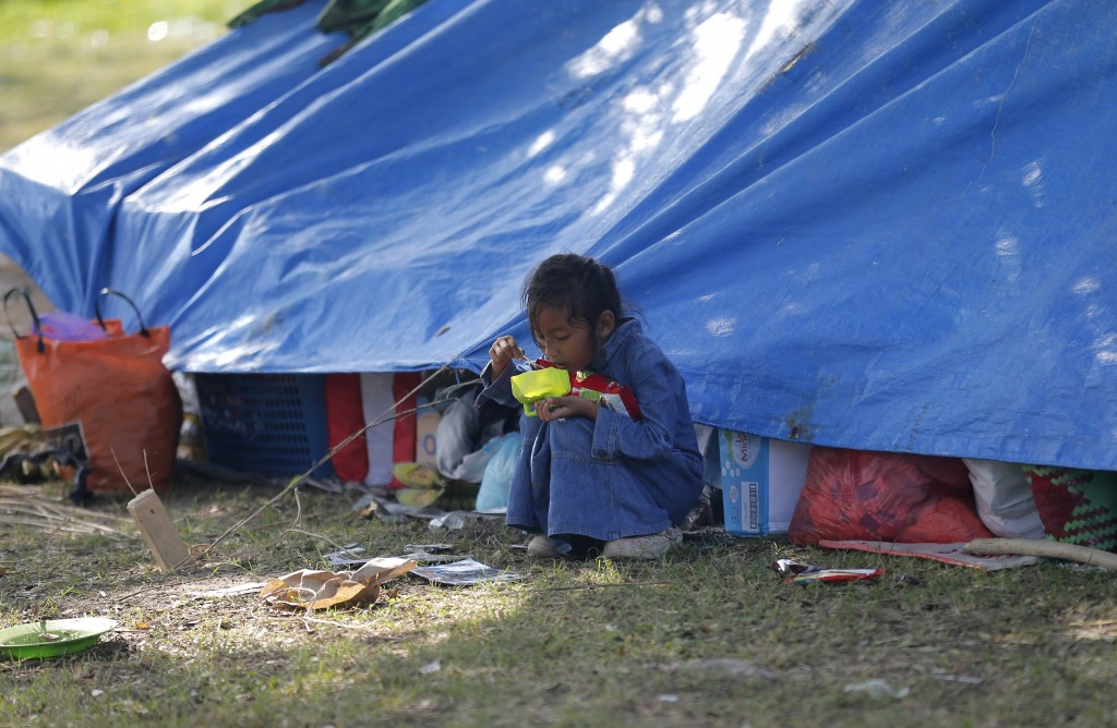A child eats some breakfast at a temporary shelter in Palu, Central Sulawesi Indonesia, Thursday, Oct. 4, 2018. Life is on hold for thousands living i...