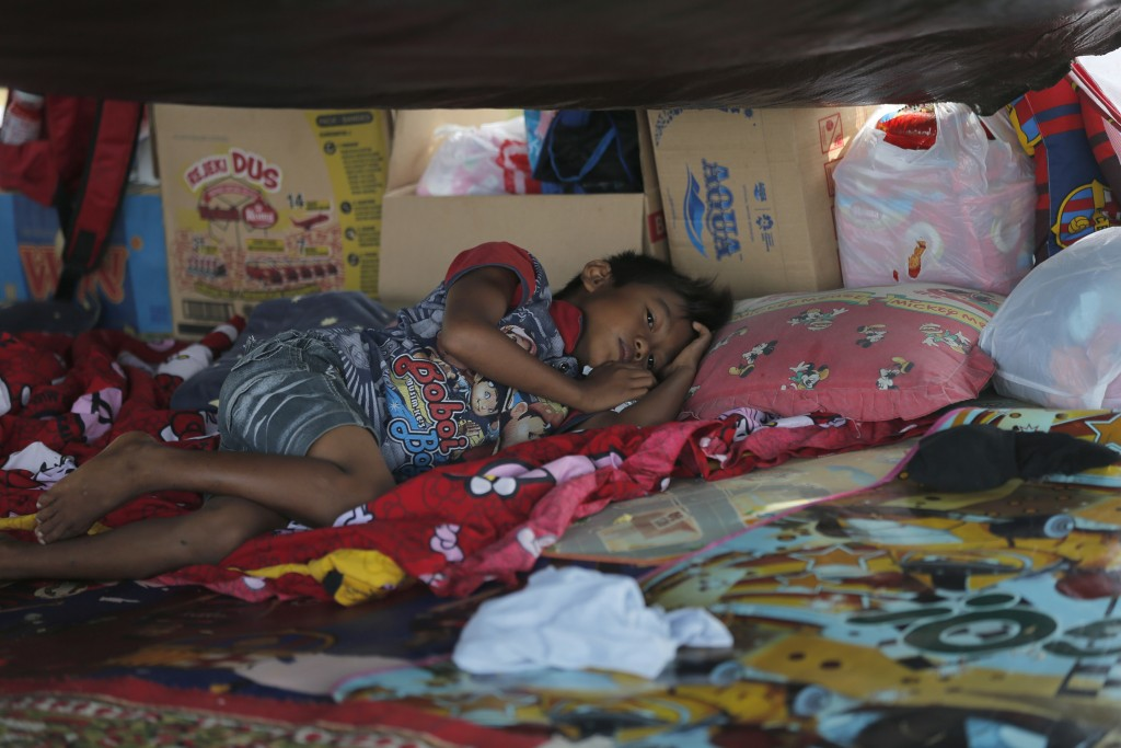 A boy sleeps inside a tent at a temporary shelter in Palu, Central Sulawesi Indonesia, Thursday, Oct. 4, 2018. Life is on hold for thousands living in...