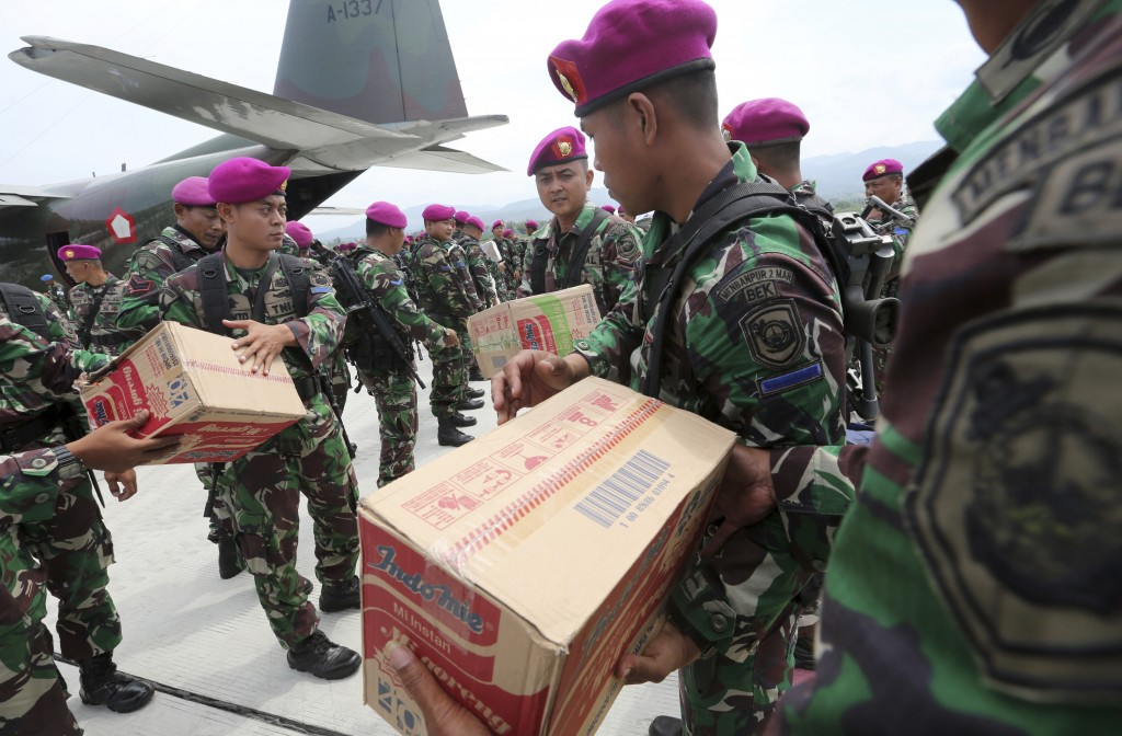 Indonesian military personnel distribute relief aid at the Mutiara Sis Al-Jufri airport to evacuate the earthquake and tsunami-damaged city of Palu, C...